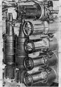 В отделении управления 5 снарядов и 7 зарядов размещены в баке-стеллаже (рис. 13), а 2 снаряда расположены вертикально в гнездах около бака-стеллажа.  В боевом отделении один снаряд 1 вертикально раз¬мещен на полу кормовой части кабины справа от загрузочного окна и один заряд 2, в специальном защитном чехле, закреплен вертикально на полу в правой передней части кабины.